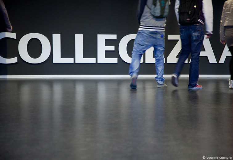 een foto van de muur in het initium waarop Collegezaal staat geschreven met onherkenbare studenten die er voor langslopen